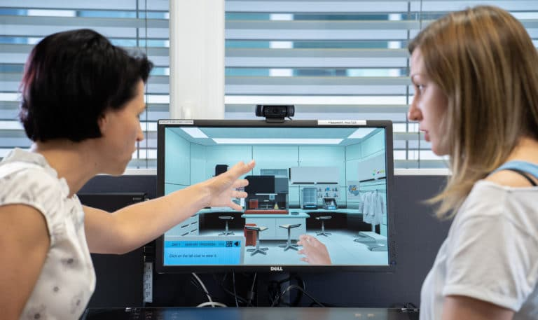 Teacher and student pointing at Labster on screen